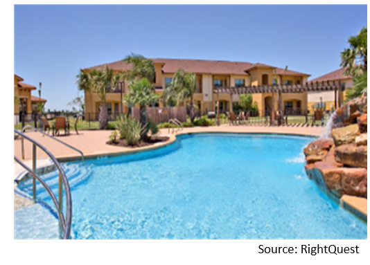 Exterior of a mexican-style apartment complex with resort-style pool on sunny day