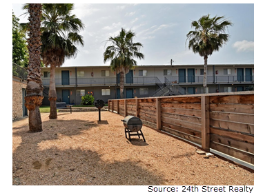 The gravel-paved grilling area of Romeria Place in the late afternoon. It is bordered by a wooden fence and palm trees