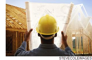 Stock photo of a many wearing a construction hat looking at blueprints.