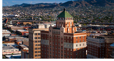 An aerial view of the historic Plaza Hotel, with the City of El Paso arrayed in the background.