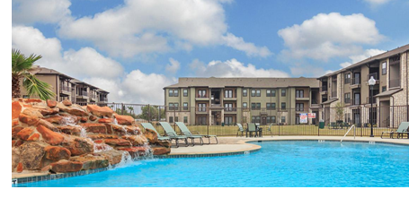 A view of one of the buildings at Vantage at Harlingen, with the community's pool in the foreground.