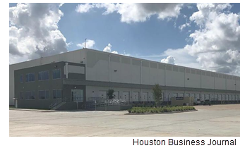 A back-lit industrial building made of concrete in Houston. It is a mostly cloudy afternoon