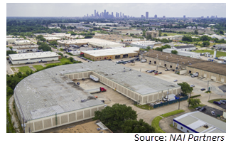 Aerial view of industrial property in houston. the city skyline is visible in the background
