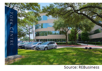 Image of the entrance to the parking lot which is surrounded by trees.