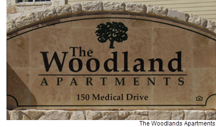 The Woodlands Apartments community street sign.