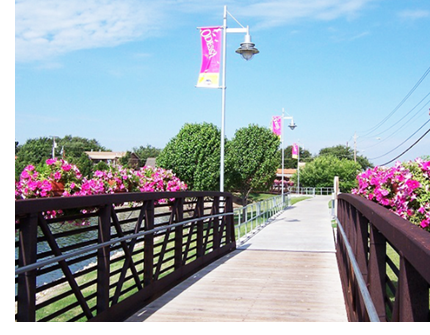 A foot bridge featuring pink flowers on the side, and banners that say