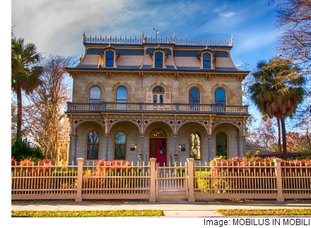 Photo: An Victorian-style house in San Antonio with a Stone exterior, and upper-floor balcony, and a gate.