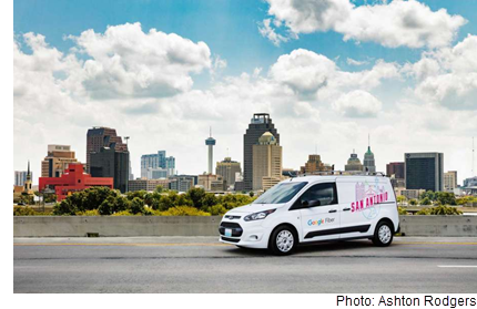 A google fiber van that says San Antonio, against the backdrop of the San Antonio skyline.