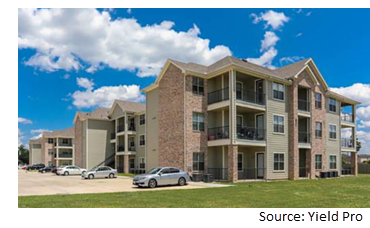 Image of one of the apartment buildings on the property with a blue sky back drop.