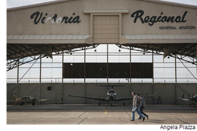 Two men walk in front of a hangar at Victoria Regional Airport.